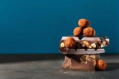 Chocolates escuros da pilha e da trufa do chocolate no fundo azul Imagem de Stock