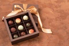 Chocolates finos na caixa do ofício com fita do cetim em um fundo escuro Lugar para o projeto Disposição lisa Conceito festivo foto de stock