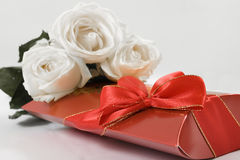 Chocolates and flowers. A box of chocolates and white roses Stock Photos