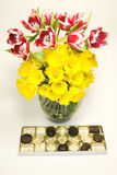 Chocolates and flowers. Yellow daffodils and pink tulips with eaten chocolates Stock Images
