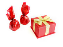 Chocolates and gift. Two red chocolates and a gift box on white background Stock Photography