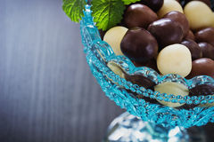 Chocolates in a glass bowl on a black wooden background. festiva Stock Photo