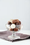 Chocolates in glass on the white wooden background Royalty Free Stock Photography