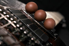 Chocolates on the guitar. Three chocolate eggs placed on the strings of a guitar stock images