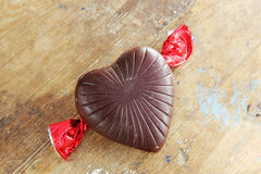 Chocolates. With heart shape on rustic wooden background Royalty Free Stock Images