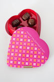Chocolates in a heart shaped box. Assorted Chocolates in a heart-shaped box on a white background Stock Image