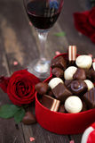 Chocolates in a heart shaped box and a bunch of red roses on woo royalty free stock photography