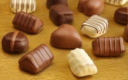 Chocolates luxuosos na placa dourada Imagens de Stock