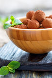Chocolates and mint in a wooden bowl. Royalty Free Stock Photography