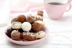 Chocolates na bacia no fundo de madeira branco Imagem de Stock
