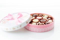 Chocolates na caixa cor-de-rosa no fundo branco Imagem de Stock Royalty Free