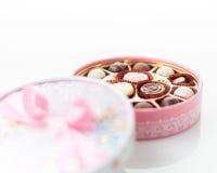 Chocolates na caixa cor-de-rosa no fundo branco Imagens de Stock