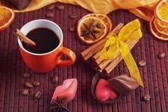 Chocolates na forma do coração e dos bordos, copo alaranjado de c preto Fotografia de Stock Royalty Free