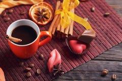 Chocolates na forma do coração e dos bordos, copo alaranjado de c preto Fotografia de Stock