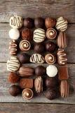 Chocolates no fundo de madeira cinzento Fotos de Stock Royalty Free