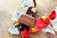 Chocolates. With other wrapped candies on rustic wooden background Royalty Free Stock Photo