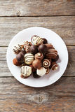 Chocolates on plate on the grey wooden background Stock Photos