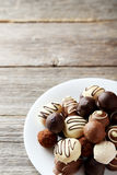 Chocolates on plate on a grey wooden background Royalty Free Stock Photography