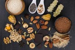 Chocolates, porcas, varas de canela e especiarias nas colheres e no c Imagens de Stock