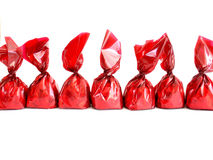 Chocolates in red. Wrapping in a row on white background Royalty Free Stock Photo