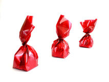 Chocolates in red. Three chocolates in red wrapping on white background Royalty Free Stock Image