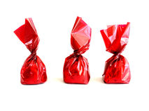 Chocolates in red. Three chocolates in red wrapping on white background Royalty Free Stock Photography