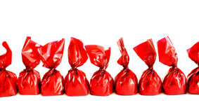 Chocolates in red. A line of chocolates in red wrapping on white background Royalty Free Stock Images