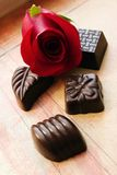 Chocolates and rose. Closeup of decorative dark chocolates and red rose over a grunge background, shallow DOF Royalty Free Stock Photos
