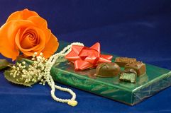 Chocolates and rose. A closeup view of a chocolates on a box with a peach rose and white necklace Stock Photography