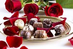 Chocolates and roses stock photos