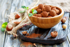 Chocolates stuffed with hazelnuts in a wooden bowl. Royalty Free Stock Image