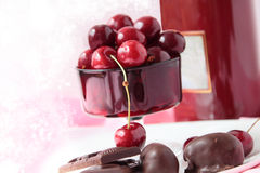 Chocolates and sweet cherry berries. Sweet cherry in a red glass and chocolates Royalty Free Stock Image