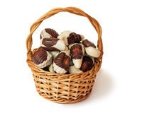 Chocolates in a wattled basket on a white background. Royalty Free Stock Photos