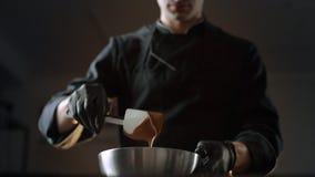 Chocolatier miesza rozciekłą czekoladę i nalewa je puchar, robić cukierki i handmade czekoladowi bary, 4k UHD zbiory