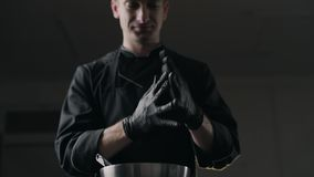 Chocolatier puts on the black rubber gloves, making of sweets and handmade chocolate bars, full hd Prores HQ 422. Chocolatier puts on the black rubber gloves stock video