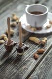 chocolats avec le thé et écrous sur le fond en bois images libres de droits