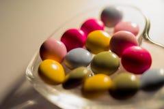 Chocolats colorés dans la plaque d'herbe Images stock