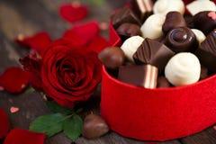 Chocolats dans la boîte et la mère en forme de coeur de fond de roses rouges Image stock