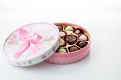 Chocolats dans la boîte rose sur le fond blanc Photo libre de droits
