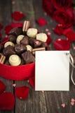 Chocolats dans une boîte en forme de coeur et un groupe de roses rouges avec c Photos stock