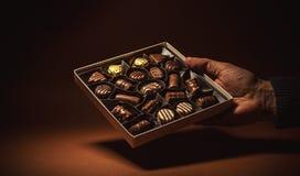 Chocolats de boîte dans une main Photos stock