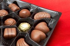 Chocolats de Valentines dans le cadre sur la soie rouge Photos stock