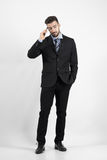 Chłodno młody biznesowy mężczyzna patrzeje daleko od na telefonie Obraz Royalty Free