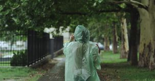 Chodząca kobieta na ulicie na podeszczowym dniu, ona jest ubranym deszczowa i trzyma niektóre mapy, tła chodzić ludzie zbiory wideo