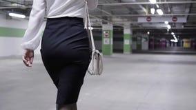 Chodząca młoda kobieta z konika ogonem, biała koszula i czerń, omijamy w garażu zdjęcie wideo