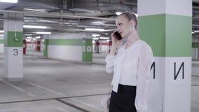 Chodząca młoda kobieta z konika ogonem w białej koszula i czerń omijamy w parking zbiory