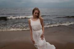 Chodz?ca Pi?kna m?oda blondynki kobiety pla?y boginka w biel sukni blisko morza z falami podczas nied?wi?cznej ponuractwo pogody  obraz royalty free