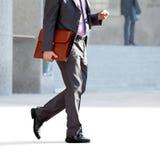 Chodzący biznesmen z teczką i notatką. Obraz Stock