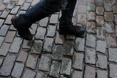 Chodzący mężczyzna ` s iść na piechotę przy mokrym brukowa kwadratem po deszczu Stara dachówkowa droga Zdjęcia Stock