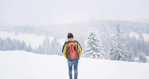 Chodzący turysta w śnieżnym lesie wyposażającym z wszystkie podróż materiałem z dużą pomarańczową torbą, podróżuje po środku zbiory